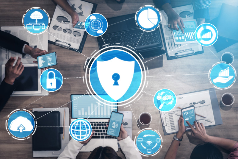 People using technology while icons related to cybersecurity are around them